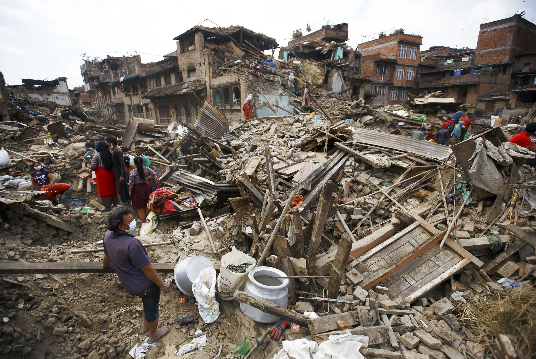 Người dân ở Bhaktapur, Nepal, lượm lặt những thứ còn sót lại trong khu nhà đổ nát sau trận động đất (Ảnh chụp 30/04/2015)