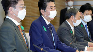 Shinzo Abe (centro) asiste a una reunión con el comité encargado de la crisis del coronavirus, todos con mascarillas, el 16 de abril de 2020 en Tokio