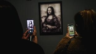 Visitors take photos of a version of the 'Mona Lisa' during the free opening of the 'Leonardo da Vinci' exhibition at the Louvre Museum on 21 February, 2020 in Paris.