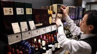 Un employé range des bouteilles de whisky japonais dans une boutique de spiritueux à Tokyo, le 26 février 2015.