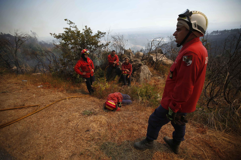 Bombeiros descansam após conseguir extinguir parte do fogo em Tondela, Portugal, em imagem do dia 25 de agosto de 2013.