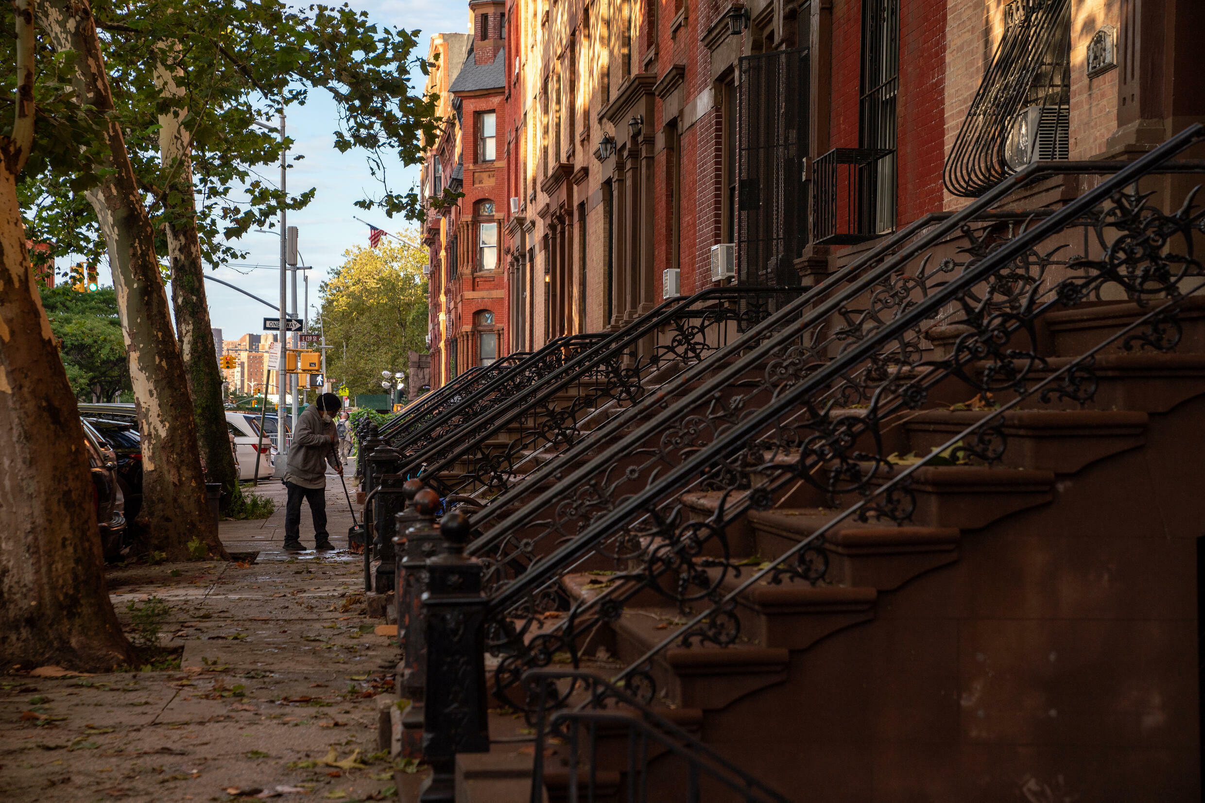 A person sweeps up debris in the front of a brownstone after the extremely heavy rainfall from Hurricane Ida on September 2, 2021, in the Bronx borough of New York City