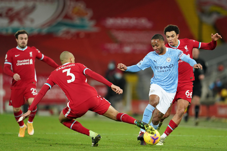 El volante del Manchester City Raheem Sterling intenta escapar de la marca del brasileño Fabinho, del Liverpool, en partido de la Premier League jugado el 7 de febrero de 2021 en Anfield