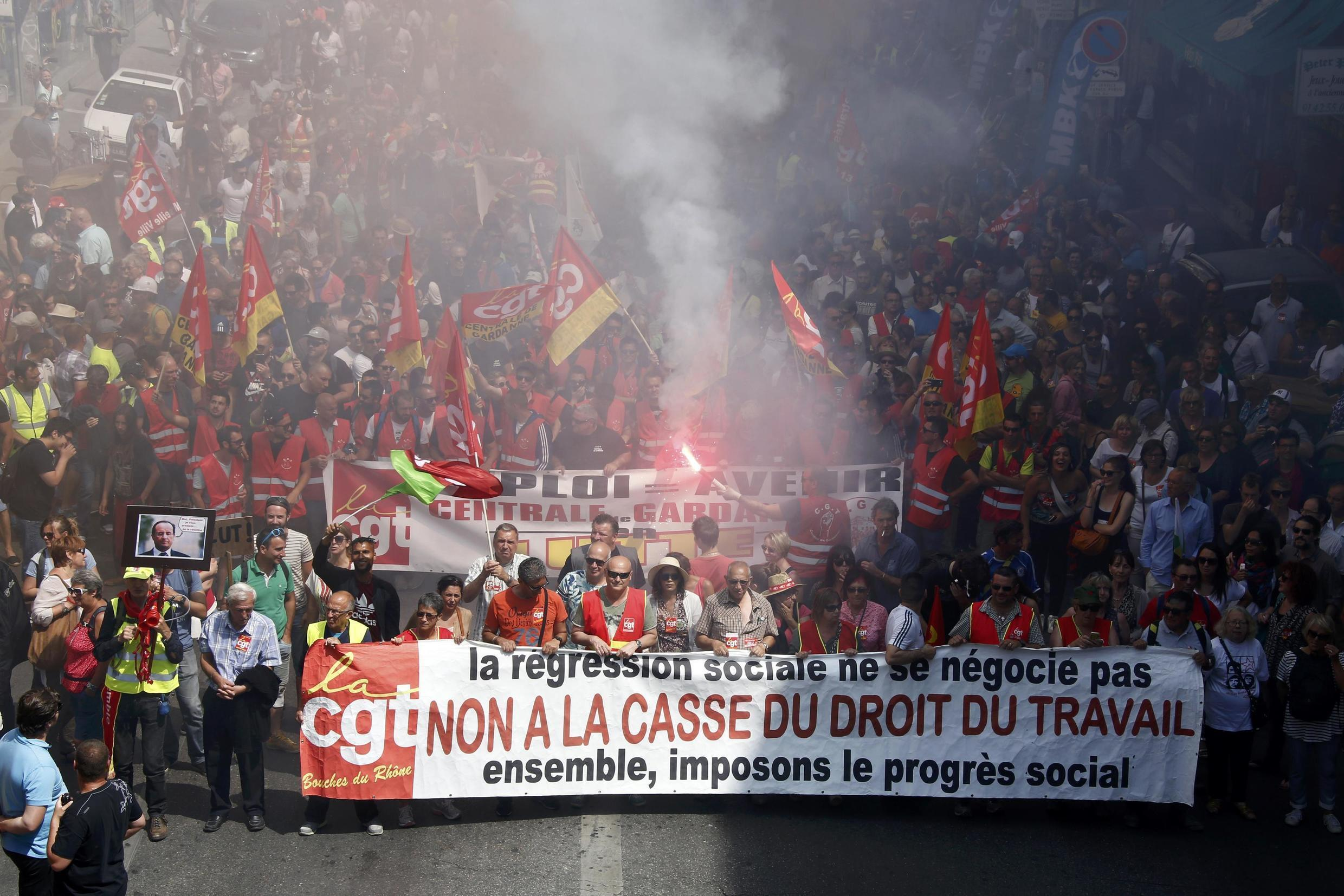 """French CGT labour union employees march during a demonstration in Marseille as part of nationwide protests against plans to reform French labour laws, France, June 14, 2016. The slogan reads """"No to the break-up of the labour law""""."""