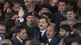 Yousuf Raza Gilani waves to supporters outside the Supreme Court