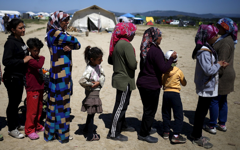 Des femmes et des enfants réfugiés font la queue pour manger près du village d'Idoméni à la frontière gréco-macédonienne, le 21 avril 2016.
