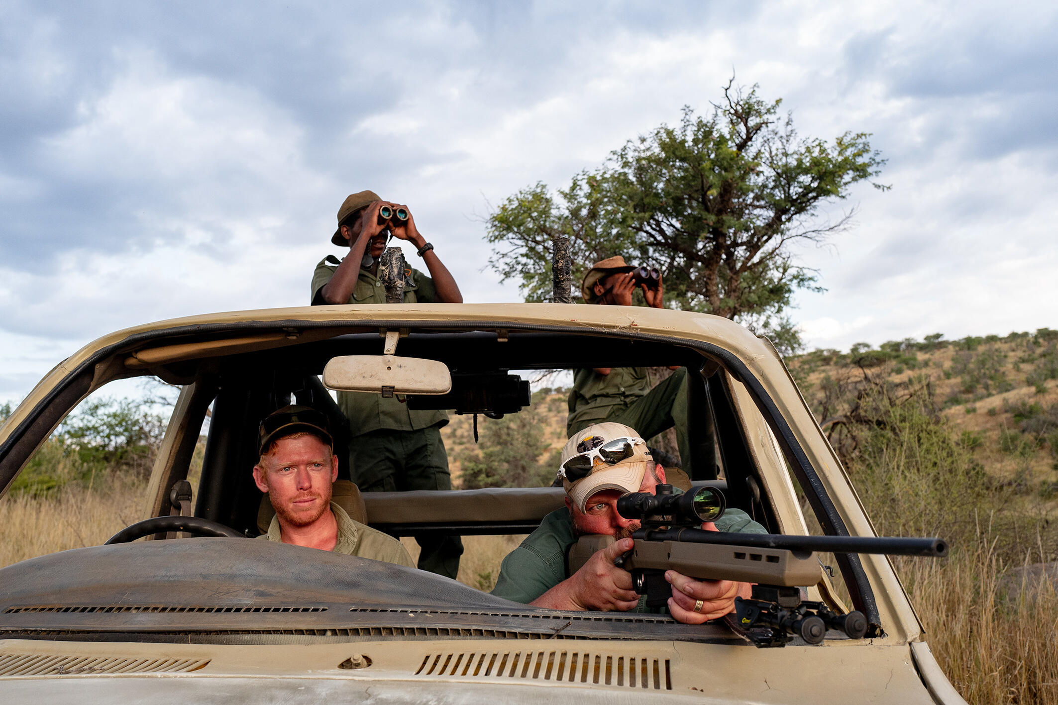 Erik Grimland in a jeep with Philip Hennings, the owner of the wild game reserve, and two guides, hunting hartebeest antelope. Khomas Highland, Namibia, April 21, 2021.