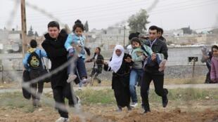 Des Syriens fuient la ville de Ras al-Ain vers la ville turque de Ceylanpinar, le 9 novembre 2012.