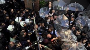 Des employés tentent de bloquer l'assaut des forces de l'ordre à l'entrée dans les locaux des chaînes de télévision Bugün et Kanaltürk, mercredi 28 octobre 2015 à Istanbul.