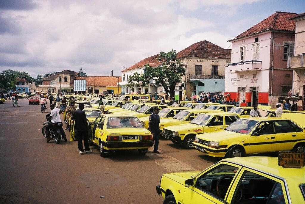 Táxis estacionados em frente ao mercado da cidade de São Tomé