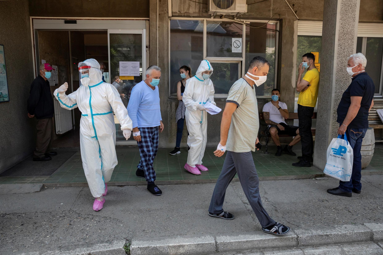 Personnel de santé d'un hôpital de Belgrade accompagnant des personnes déclarées positives au Covid-19, le 26 juin 2020.