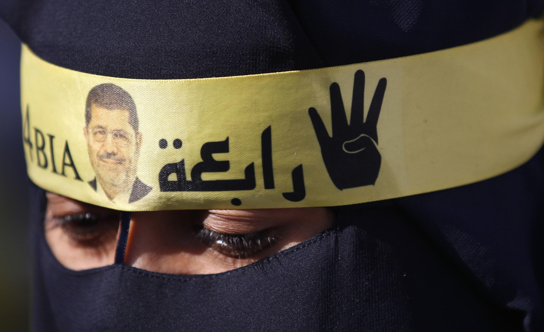 Một thành viên Huynh Đệ Hồi Giáo quấn băng có hình cựu Tổng thống Morsi