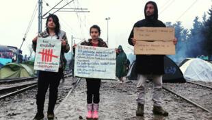 Ali le jeune Syrien qui a fui Damas. Ici à Idomeni, aux côtés de deux petites réfugiées, avec une pancarte « Je ne suis pas un terroriste ».