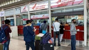 Des voyageurs attendent pour acheter des billets d'avion à l'aéroport international Indira Gandhi, lors du premier jour de reprise du trafic domestique en Inde, à New Delhi le 25 mai 2020.