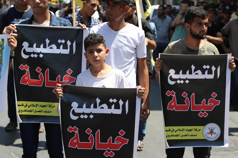 """فلسطینیان در یک راهپیمایی در غزه، با حمل پلاکاردهایی که بروی آن """"عادی سازی خیانت است"""" نوشته شده بود، به توافق امارات متحده عربی با اسرائیل اعتراض کردند. جمعه ۲۴ مرداد/ ۱۴ اوت ۲۰۲۰"""