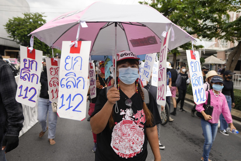 Une manifestante pro-démocratie défile avec une pancarte appelant à abolir l'article 112 sur le lèse-majesté en Thaïlande, le 24 juin 2021.
