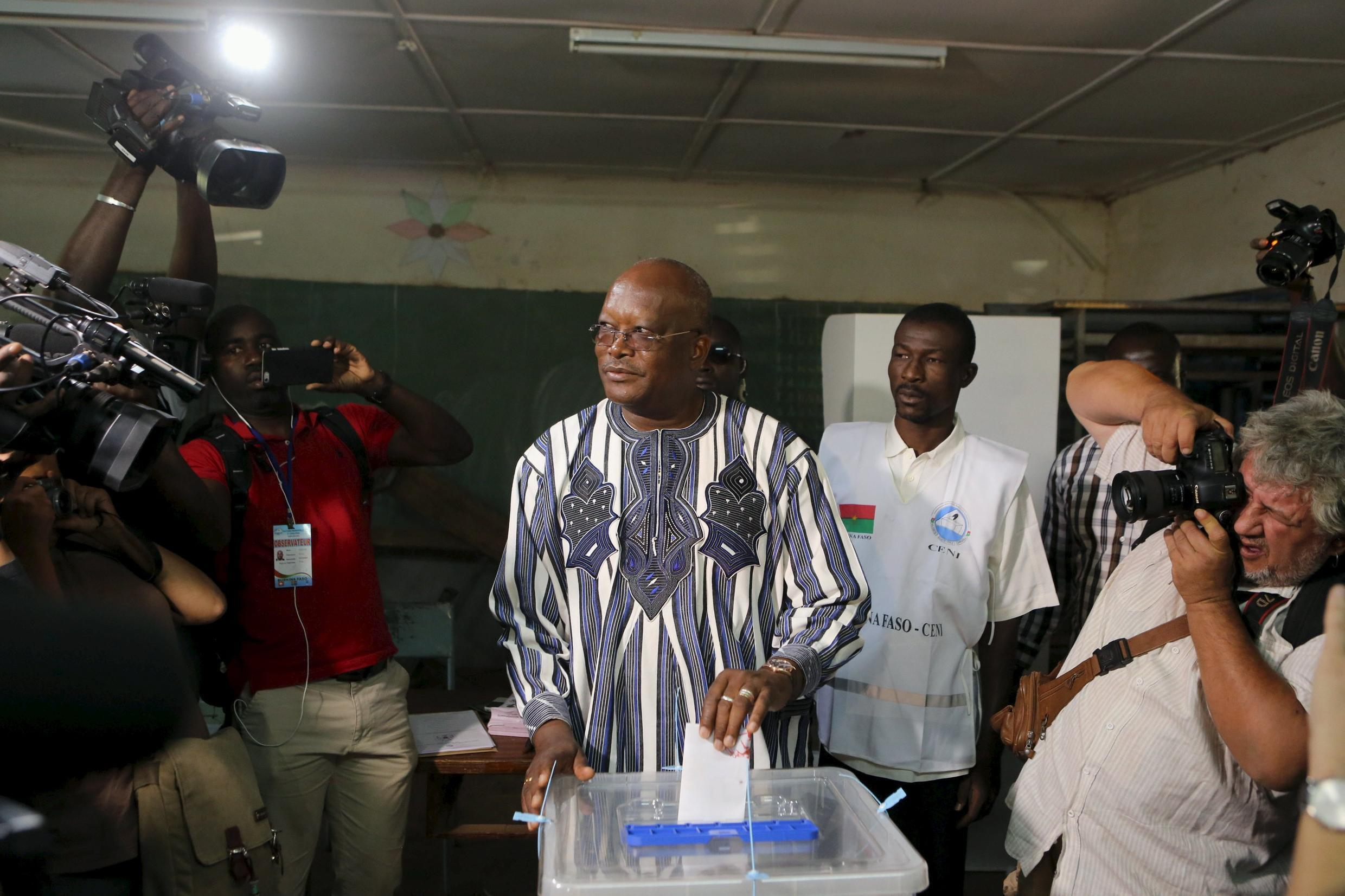Presidential candidate Roch Marc Kabore (c) votes during the presidential and legislative election at a polling station in Ouagadougou, Burkina Faso, November 29, 2015.