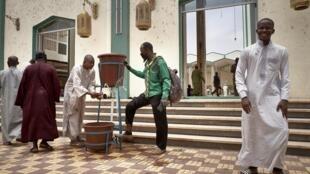 Un scout appelle aux fidèles de se laver les mains avant d'entrer dans la grande mosquée de Bamako lors de la prière du vendredi 10 avril 2020.