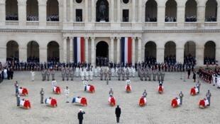 O presidente francês Emmanuel Macron presta homenagem em frente aos caixões decorados com bandeiras dos treze soldados franceses mortos no Mali, durante uma cerimônia no Hotel National des Invalides em Paris, França, em 2 de dezembro de 2019.