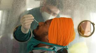 Un técnico sanitario toma una muestra de mucosa nasal a un hombre para hacer una prueba de detección del coronavirus, el 24 de mayo de 2021 en Amritsar, al norte de la India