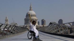 Un joueur de handibasket britannique, Ade Adepitan, porte la flamme olympique à Londres.
