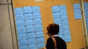 Una mujer mira los anuncios de una agencia para el empleo en Gijón, España.