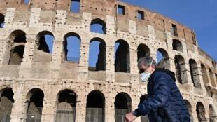 Un homme portant un masque passe devant le Colisée à Rome, le 10 mars 2020.