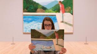 Une jeune femme pose à côté d'une œuvre d'art intitulée «Portrait d'un artiste (Pool with two figures), 1972» par l'artiste britannique David Hockney.