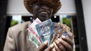 Wani dan Sudan ta Kudu dauke da kudin kasar na Fam a wajen babban bankinsu da ke birin Juba.