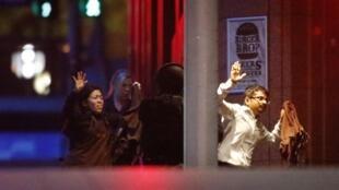 Des otages s'échappent du café après 16 heures de prise d'otage, le 15 décembre 2014.