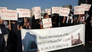 Des personnes portant des pancartes et des photos de membres de leur famille et d'amis tués dans l'explosion massive du 4 août dernier au port de Beyrouth, sont rassemblées pour réclamer justice.