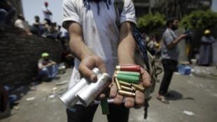 Manifestante pró-Mursi exibe cápsulas das balas que teriam sido disparadas pelo exército egípcio
