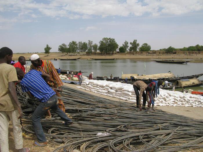 Chargement et déchargement des marchandises (sacs de riz...) au port de Korioumé à Tombouctou au Mali. Image d'illustration.