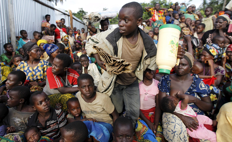 Burundian refugees rest with their belongings on the shores of Lake Tanganyika in Kagunga village, in western Tanzania's Kigoma region