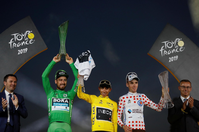 Sur le podium du Tour de France 2019 : le maillot vert slovaque Peter Sagan, Egan Bernal qui cumule maillot jaune et maillot blanc, et le Français Romain Bardet qui s'adjuge le maillot à pois.
