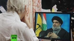 "Julian Assange (de costas) em entrevista com chefe do Hezbollah na estréia de seu programa ""The World Tomorrow""."