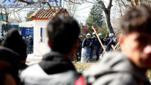 Des migrants face aux forces anti-émeutes à la frontière turco-grecque, près de Kastanies, le 1er mars 2020.