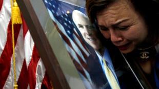 Một phụ nữ Mỹ gốc Việt khóc thương John McCain trước di ảnh của thượng nghị sĩ ở Đại sứ quán Hoa Kỳ tại Hà Nội, ngày 27/08/2018.