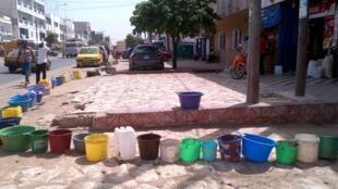 Une file d'attente de seaux devant une pompe à Dakar, Sénégal.