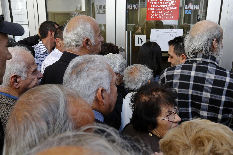 Des clients de Laiki bank attendent pour rentrer dans leur agence, le 28 mars à Nicosie.