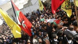 Mourners carry the body of Palestinian Haitham Yasin during his funeral in the West Bank village of Aseera Ashamaliya.