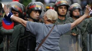 Una manifestante frente a un agente de la Guardia Nacional el 17 de febrero en Caracas, durante una marcha de protesta contra el gobierno de Nicolás Maduro.