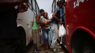 Un hombre se despide de su familia que toma un autobús para ser evacuada ante la llegada del huracán Mattheu en Secilia, el 3 de octubre de 2016.