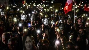 Manifestantes con el retrato de la periodista asesinada Daphne Caruana Galizia, frente a la oficina del Primer ministro Joseph Muscat,  La valette, el 29 noviembre 2019.