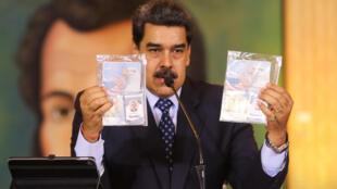 El presidente venezolano Nicolás Maduro muestra los pasaportes de dos ciudadanos estadounidenses detenidos por las fuerzas de seguridad, el 6 de mayo de 2020 durante una reunión de videoconferencia con corresponsales internacionales, en el Palacio Presidencial de Miraflores en Caracas