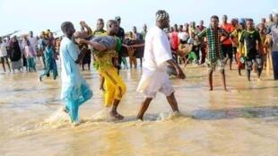 Hombres transportando un cadáver encontrado en el río Níger a su paso por la localidad de Ngaski, en Nigeria, el 26 de mayo de 2021 tras un naufragio