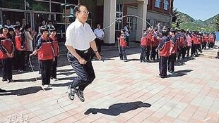 中國前總理溫家寶罕見現身官方報道  圖為他訪問河北六道河中學時與學生一起跳繩的照片