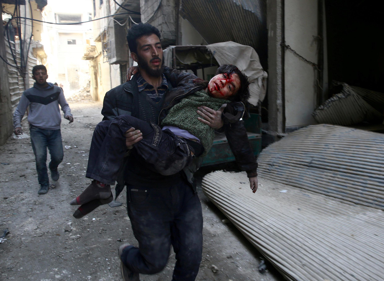 Mohammed Abu Anas corre com um garoto ferido após bombardeio em Guta Oriental.