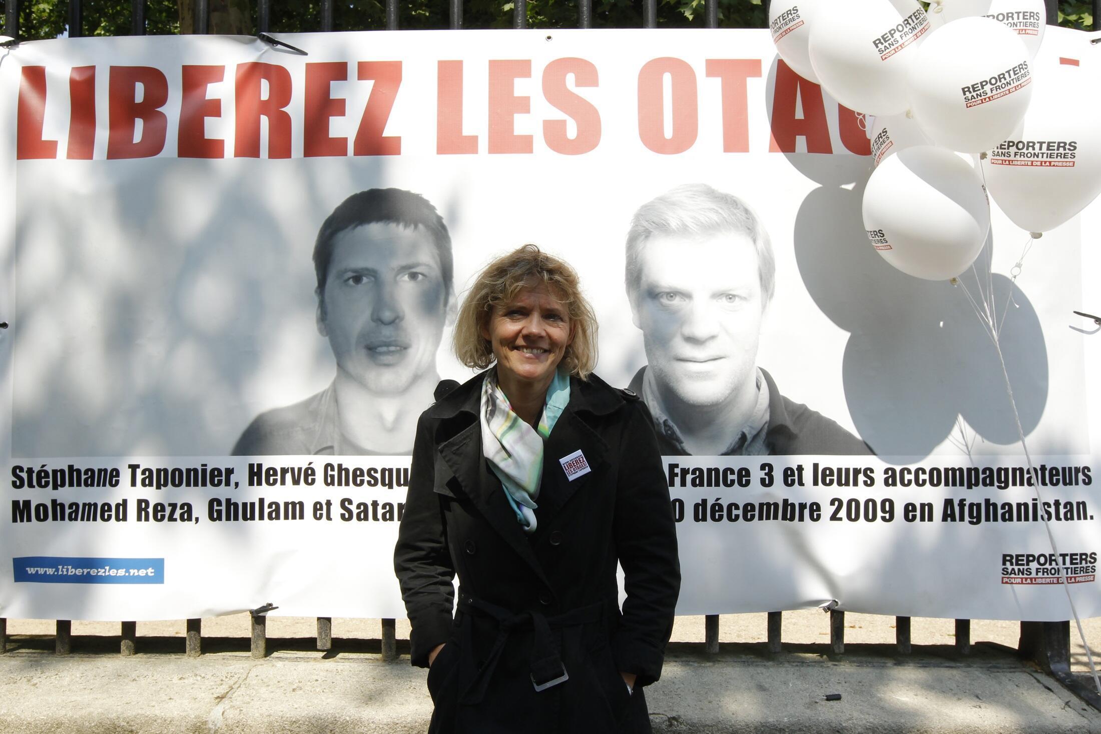 Журналистка Флоранс Обена, бывшая заложницей в Ираке, у плаката в поддержку С. Тапонье и Эрве Гескьера