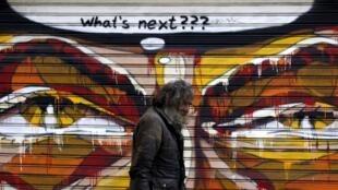 """""""E agora?"""" questiona o autor deste graffiti pintado numa parede de Atenas esta terça-feira, 14 de Julho."""